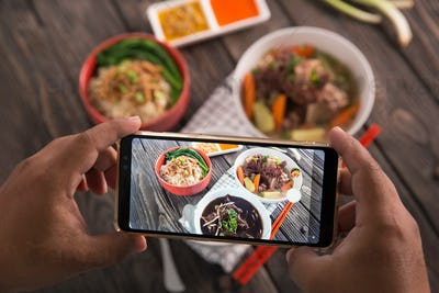 hand taking picture of delicious traditional food