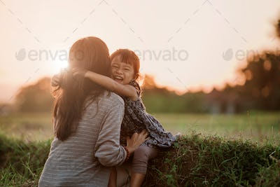 mom and kid hugging under the sunset sky