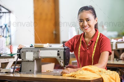 Seamstress in textile factory smiling while  sewing with indust