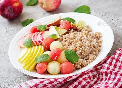 Healthy breakfast. Buckwheat or porridge with fresh melon, watermelon, apple and pear. Tasty food.