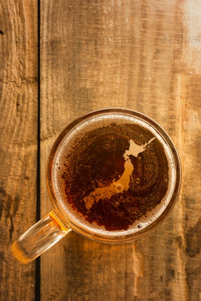 japanese beer concept, silhouette on foam in beer glass on wooden table.