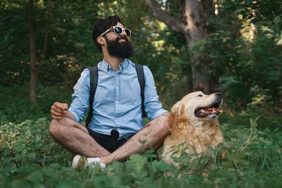 Man resting on the grass sitting crossed legs with his dog