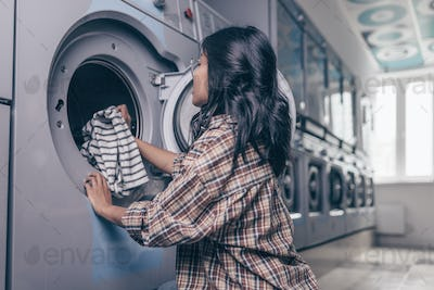 Attractive girl by the washing machine