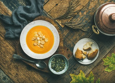 Warming pumpkin cream soup with croutons and seeds