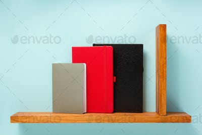 notepad and book on shelf at wall background