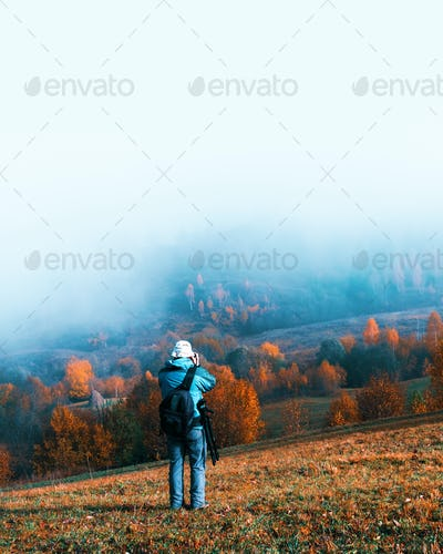 Photographer taking photo of autumn landscape