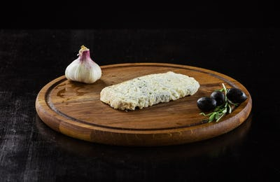 Piece of cheese with mold, garlic and olives on wooden board