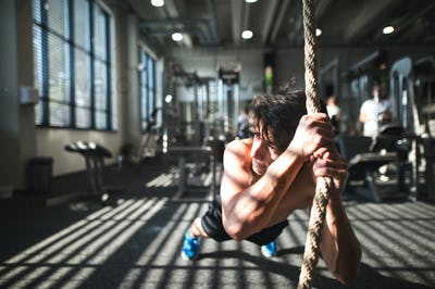 Fit young man in gym working out with climbing rope.