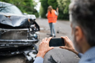 Unrecognizable man taking pictures of a broken car after an accident.