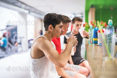 Men in gym sitting and holding glasses of protein drink.