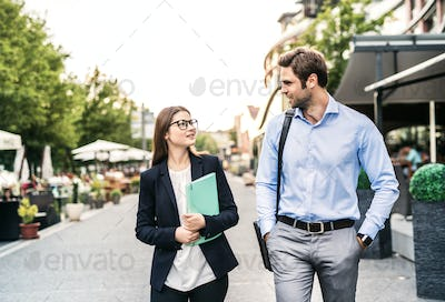 A young businessman and businesswoman walking on a sidewalk.