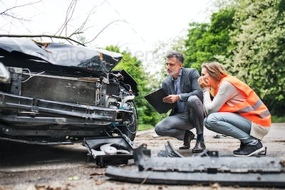 An insurance agent and a woman driver looking at the car on the road after an accident.