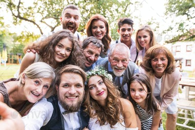 Bride, groom with guests taking selfie at wedding reception outside in the backyard.