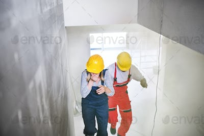 Woman and man workers running up the stairs at the construction site.