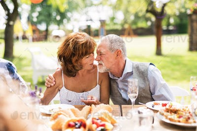 Senior couple sitting at the table on a garden party, touching noses.