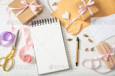 Flat lay and top view of a blank notebook and invitations on a white wooden tabletop, copy space.
