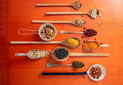 Top view of fflat lay of assortment of legumes on orange tabletop background, in scoop and ladles.