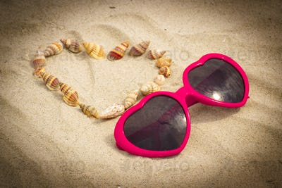 Heart of shells and sunglasses on sand at beach