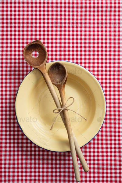 Empty plate, wooden kitchen utensils and red tablecloth on wooden table, top view