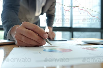 Business concepts,Businessman holding a pen pointing at a graph.