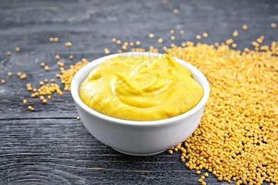 Sauce mustard in bowl on board