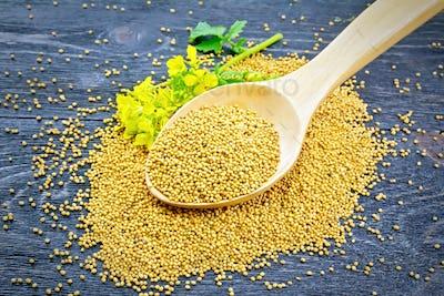 Mustard seeds in wooden spoon with flower on board