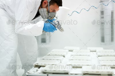 Painter using airbrush to paint wearing protective clothing