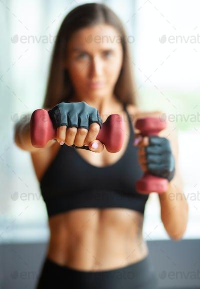 hands with dummbells, defocused sportswoman