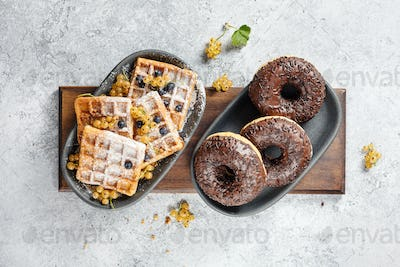 Chocolate donuts and Belgian waffles, top view.