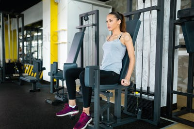 Young woman exercising on machine in gym