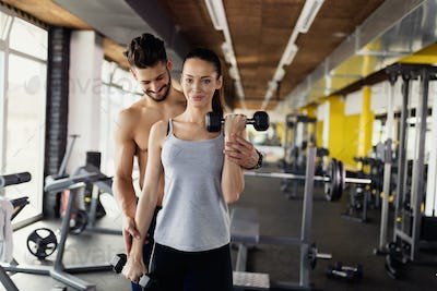 Young sexy woman doing exercises in gym with trainer