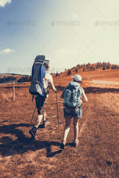 Young couple hike in mountains with baby carrier and backpacks
