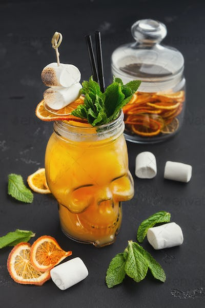 Orange cocktail in skull glass