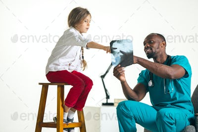 Young african male pediatrician explaining X-ray to child