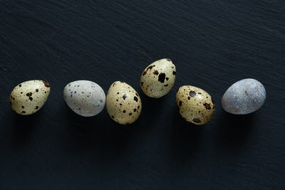 Top flatview of row of quail eggs on black stone surface