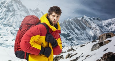 Mountaineer in winter clothes with hiking equipment against snowy landscape