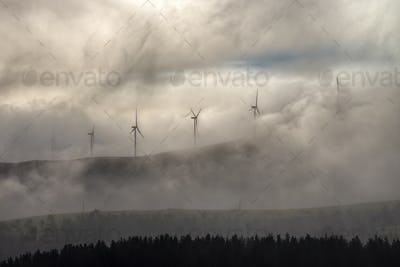 Wind turbines of a wind farm in the fog