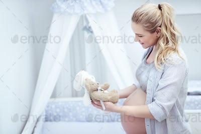 Happy mother prepares child's room