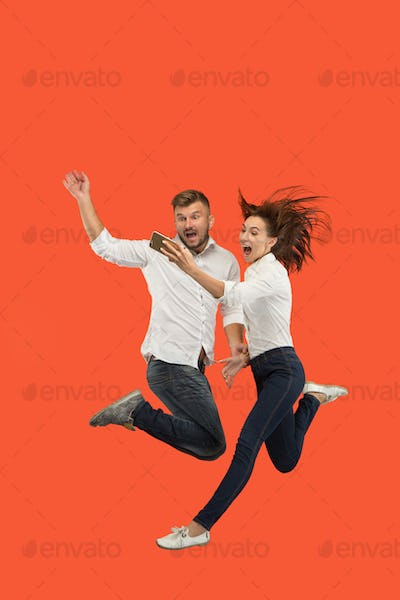 Full length of young couple with mobile phone while jumping