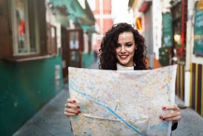Young beautiful woman looking at city map