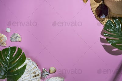seashells on pastel violet background with straw hat - summer holiday background.