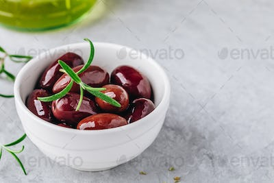 Fresh black olives in olive oil in white bowl with rosemary on gray stone background.