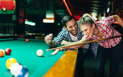 Young couple playing snooker together in bar