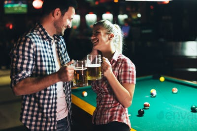 Young attractive couple on date in snooker club