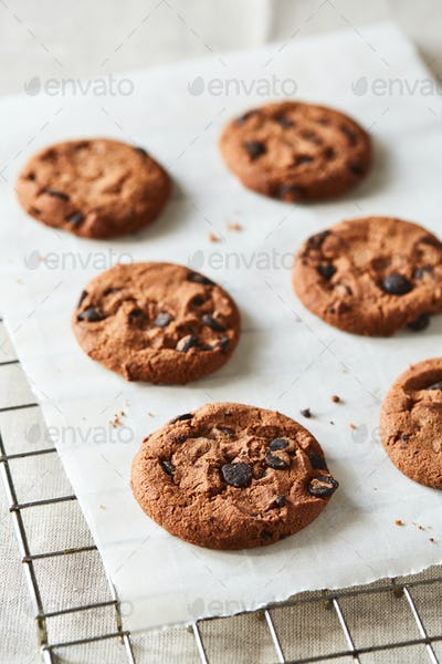Chocolate cookies with chocolate chips on baking paper