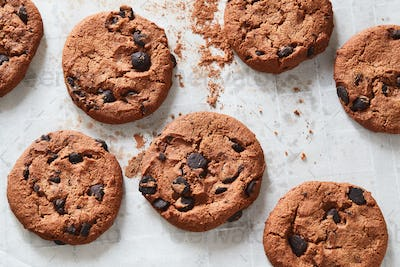 Flatview of chocolate cookies with chocolate chips and tea spoon