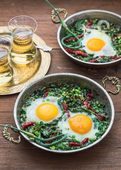Green shakshuka. Fried eggs with fresh spinach, ramson, leek in a pan on a gray background, top view
