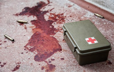 Military firs aid kit on floor with blood stains