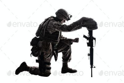 Sad soldier kneeling because of friend death