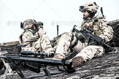 Army marksman sitting on roof observation post
